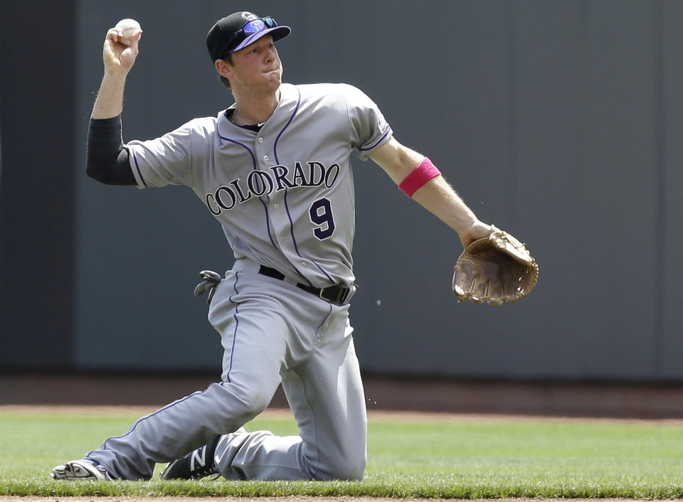 Photo - Colorado Rockies second baseman DJ LeMahieu throws to first for the out after fielding a ground ball hit by Cincinnati Reds' Joey Votto in the fourth inning of a baseball game, Sunday, May 11, 2014, in Cincinnati. (AP Photo/Al Behrman)