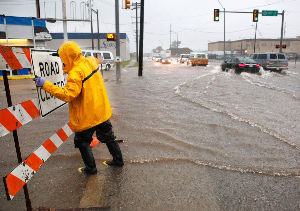 "An Oklahoma City worker attaches a ""road closed"" sign to a barricade Monday to warn motorists of roads made impassable by flooding.   Photo By Jim Beckel, The Oklahoman"