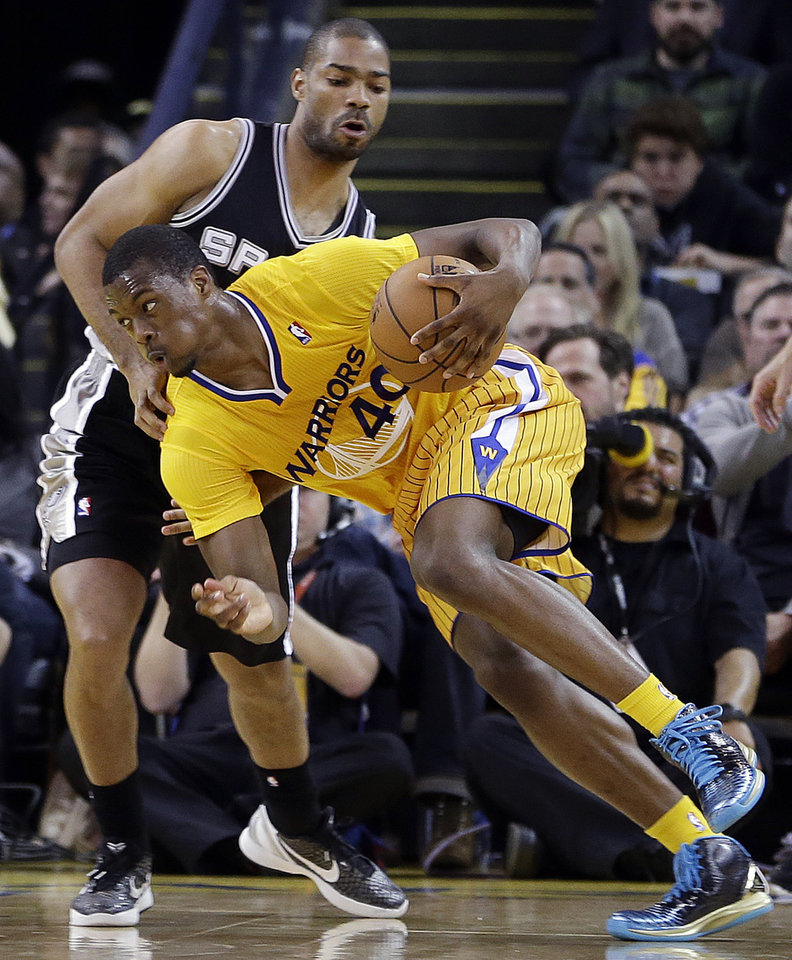 Photo - Golden State Warriors' Harrison Barnes (40) drives the ball past San Antonio Spurs' Gary Neal during the first half of an NBA basketball game Friday, Feb. 22, 2013, in Oakland, Calif. (AP Photo/Ben Margot)