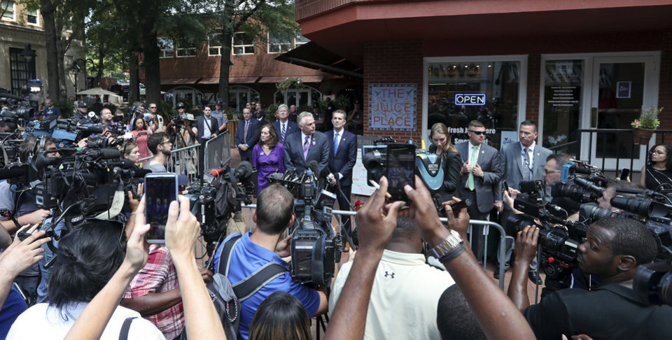 Photo - Virginia Gov. Terry McAuliffe, center, speaks with the media after a memorial service for Heather Heyer, Wednesday, Aug. 16, 2017, in Charlottesville, Va. Heyer was killed Saturday, when a car rammed into a crowd of people protesting a white nationalist rally. (Andrew Shurtleff/The Daily Progress via AP)