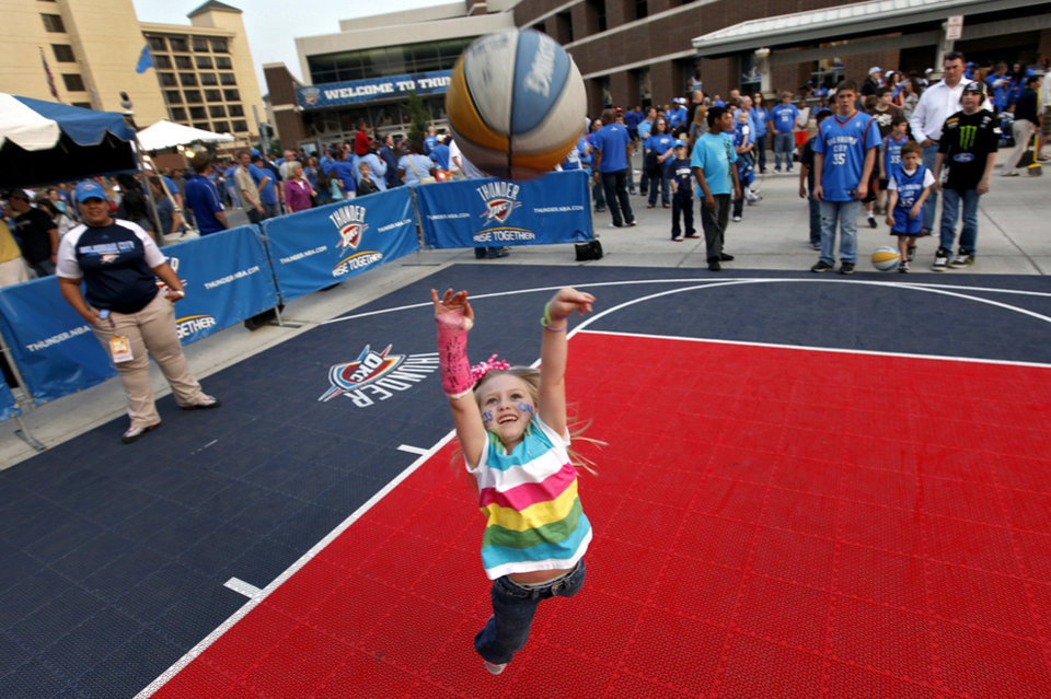 Photo - Briley Hedrick, 5, of Binger, shoots the basketball while having fun in the fan fest before the start of the first round NBA playoff game between the Oklahoma City Thunder and the Denver Nuggets on Sunday, April 17, 2011, in Oklahoma City, Okla. Photo by Chris Landsberger, The Oklahoman