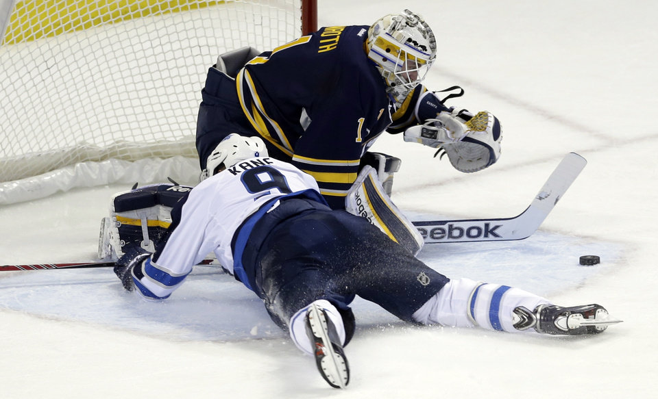 Photo - Buffalo Sabres goalie Jhonas Enroth of Sweden makes a save on a shot by Winnipeg Jets' Evander Kane (9) during the first period of an NHL hockey game in Buffalo, N.Y., Monday, April 22, 2013. Kane was tripped on the play and awarded a penalty shot. (AP Photo/David Duprey)