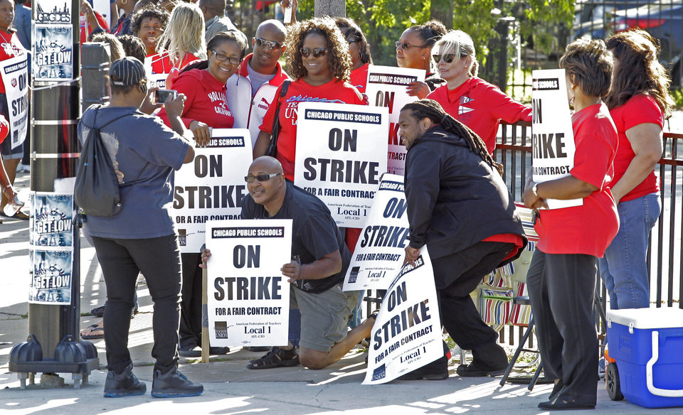 Photo -   Chicago public school teachers take a group picture as they walk a picket line outside Shoop Elementary School in Chicago, Tuesday, Sept. 11, 2012, on the second day of a strike in the nation's third-largest school district as negotiations by the two sides failed to reach an agreement Monday in a bitter contract dispute over evaluations and job security. (AP Photo/M. Spencer Green)