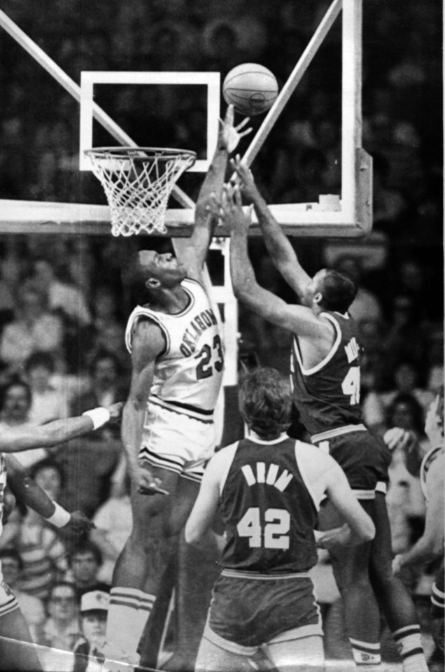 Photo - Former OU basketball player Wayman Tisdale. Oklahoma's Wayman Tisdale (left) blocks a shot by UAB forward Jerome Mincy as Lex Drum (42) watches during the Sooners' 71-63 victory in the Mideast Regional on Friday. (AP LaserPhoto) Photo taken unknown, Photo published 3/20/1983  in The Daily Oklahoman. ORG XMIT: KOD