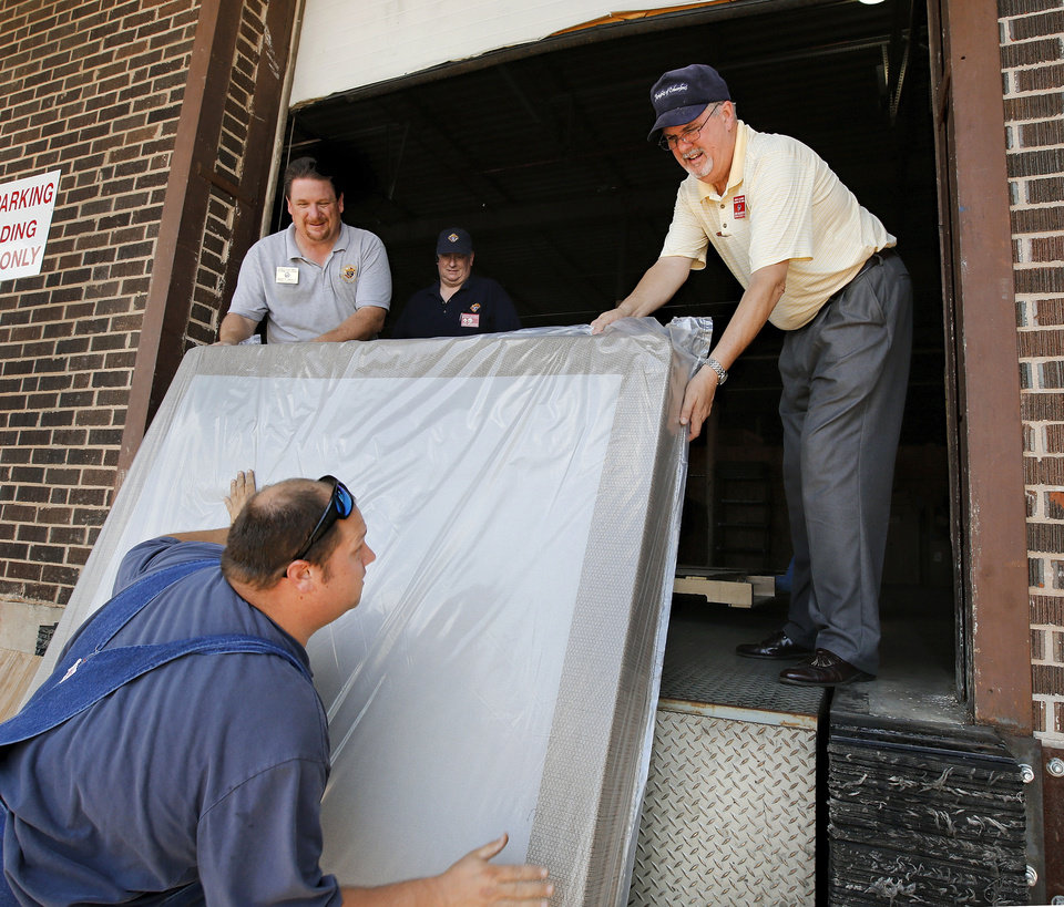 Photo - Knights of Columbus members Matt Maly, left, and John McCarthy, right, help Brian Dillon load a mattress. Dillon's home was destroyed by a tornado in May.   Jim Beckel - THE OKLAHOMAN