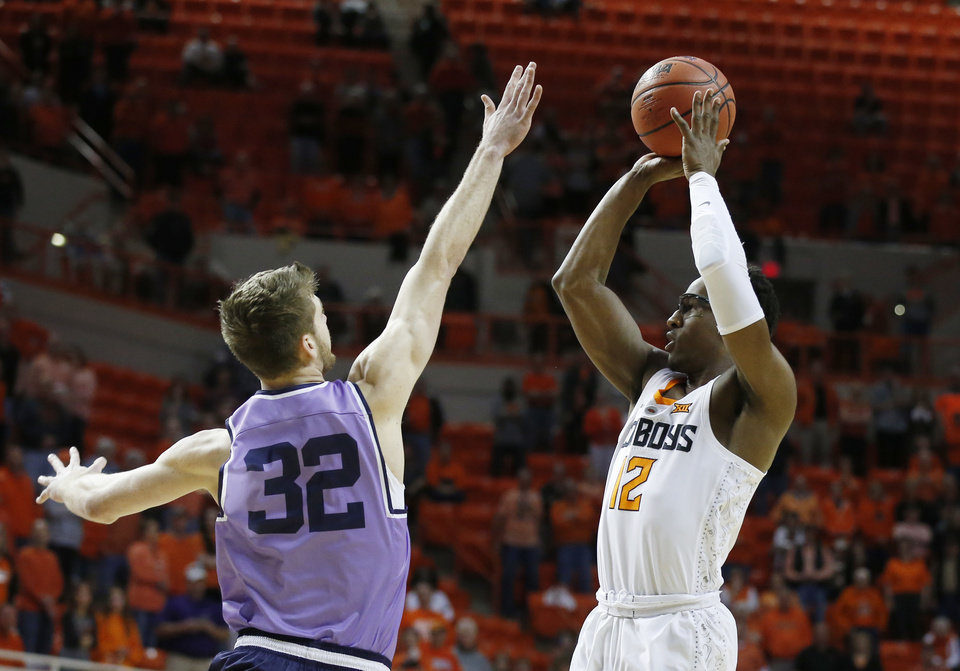 Photo - Oklahoma State forward Cameron McGriff (12) shoots as Kansas State forward Dean Wade defends during the first half of an NCAA college basketball game in Stillwater, Okla., Wednesday, Feb. 14, 2018. (AP Photo/Sue Ogrocki)