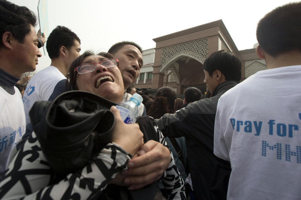 Photo - A relative of Chinese passengers on board a missing Malaysia Airlines plane breaks down as she protests outside the Malaysia Embassy in Beijing, China, Tuesday, March 25, 2014. Furious over Malaysia's handling of the lost jetliner a day after the country said the passengers must be dead, Chinese relatives of the missing marched Tuesday to the Malaysia Embassy, where they threw plastic water bottles, tried to rush the gate and chanted,