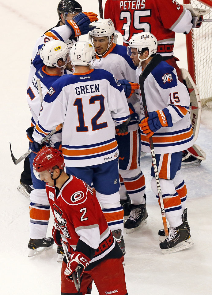 Oklahoma City\'s Jonathan Cheechoo (18) gets a pat on the helmet by Brett Clark (5) after scoring a goal as Josh Green (12) and Philippe Cornet (15) join in the celebration during an AHL hockey game between the Charlotte Checkers and the Oklahoma City Barons at the Cox Convention Center in Oklahoma City, Friday, Feb. 1, 2013. At lower left is Charlotte\'s Rasmus Rissanen (2). Photo by Nate Billings, The Oklahoman