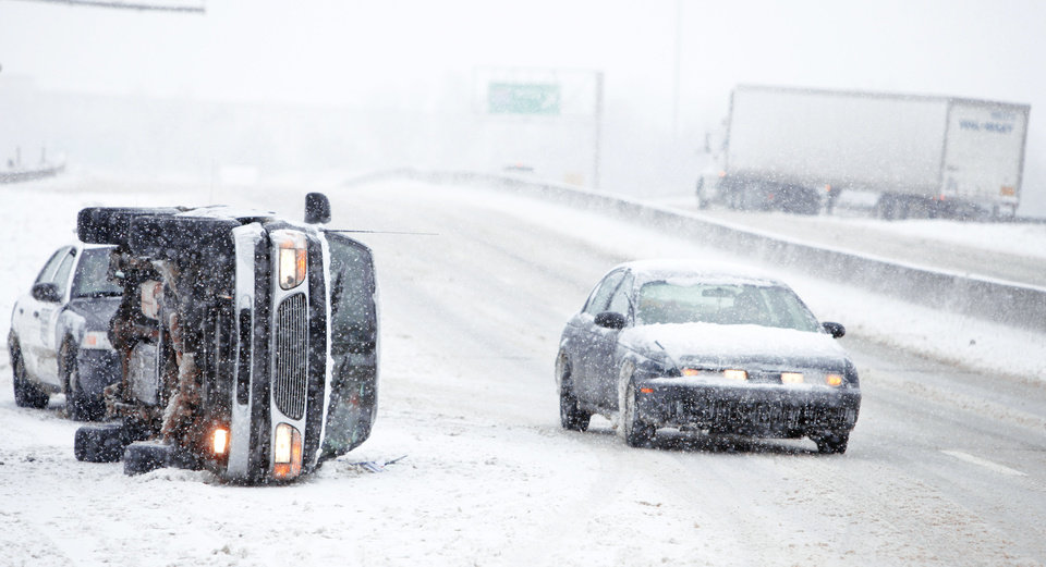 Photo - A motorist drives around an overturned vehicle Friday on the Broadway Extension near Interstate 44 in Oklahoma City. Photo by Steve Gooch, The Oklahoman