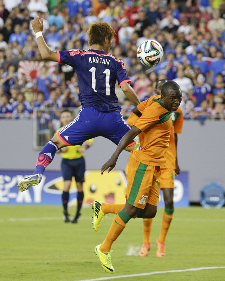 Photo - Japan's Yoichiro Kakitani (11) and Zambia's Emmanuel Mbola, right, go up for control of the ball during the first half of an international friendly soccer match in Tampa, Fla., Friday, June 6, 2014. (AP Photo/John Raoux)