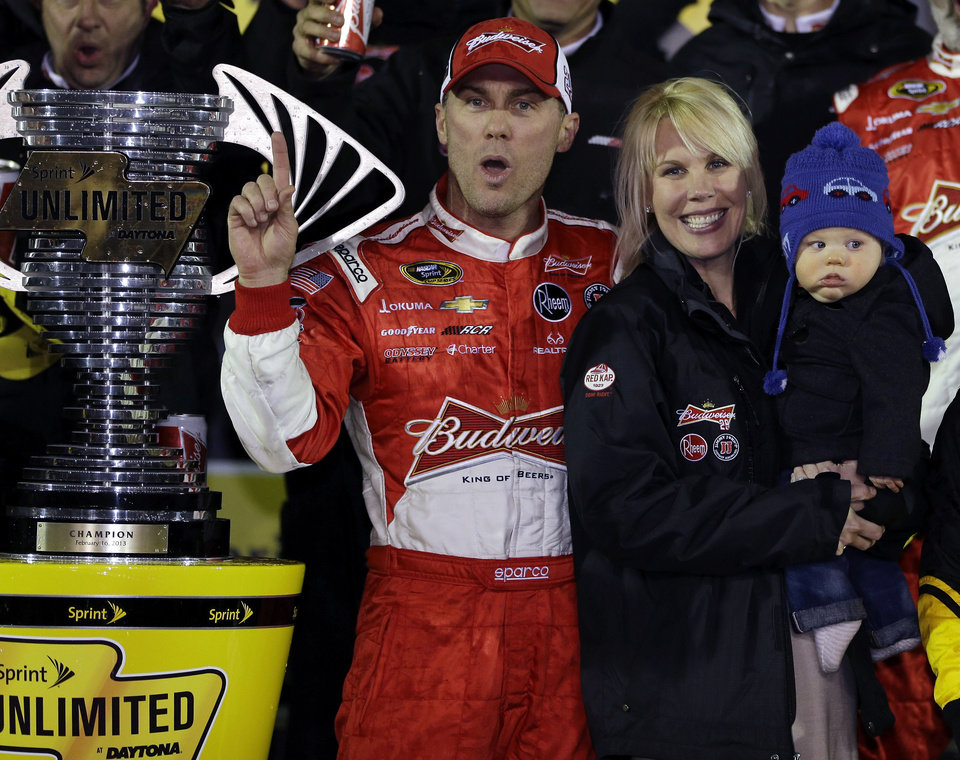 Kevin Harvick celebrates with his wife, Delana, and daughter, Keelan, 7 months, in Victory Lane after winning the NASCAR Sprint Unlimited auto race at Daytona International Speedway, Saturday, Feb. 16, 2013, in Daytona Beach, Fla.(AP Photo/John Raoux)