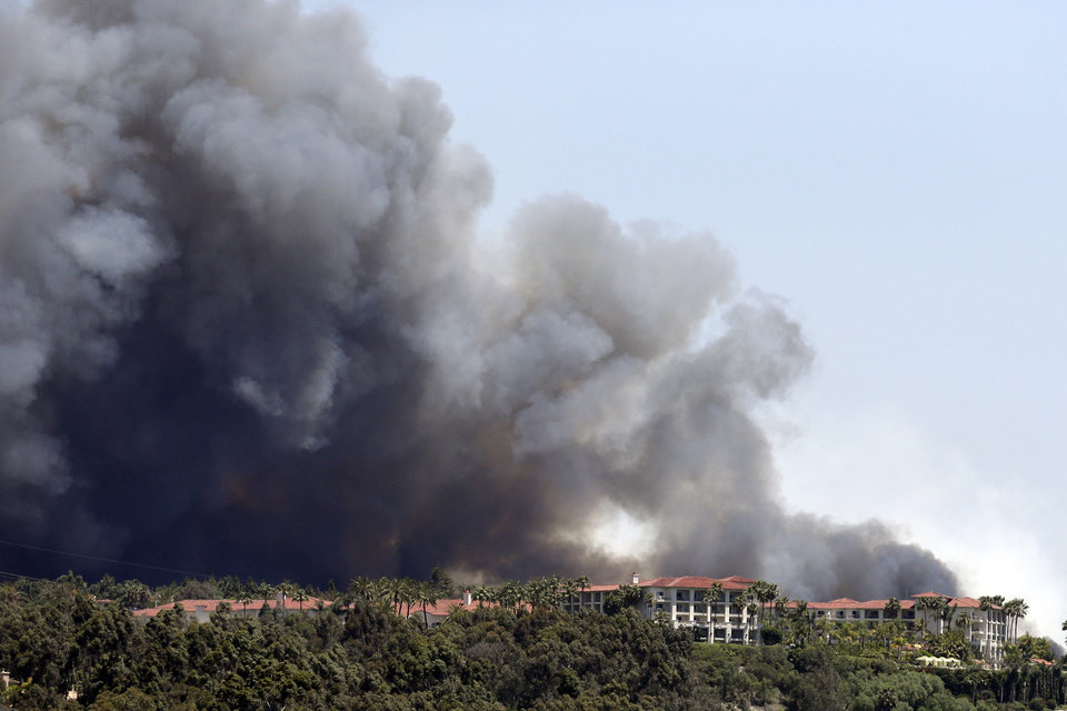 Photo - Wildfire approaches buildings Wednesday, May 14, 2014, in Carlsbad, Calif. More wildfires broke out Wednesday in San Diego County — threatening homes in Carlsbad and forcing the evacuations of military housing and an elementary school at Camp Pendleton — as Southern California is in the grip of a heat wave. (AP Photo)