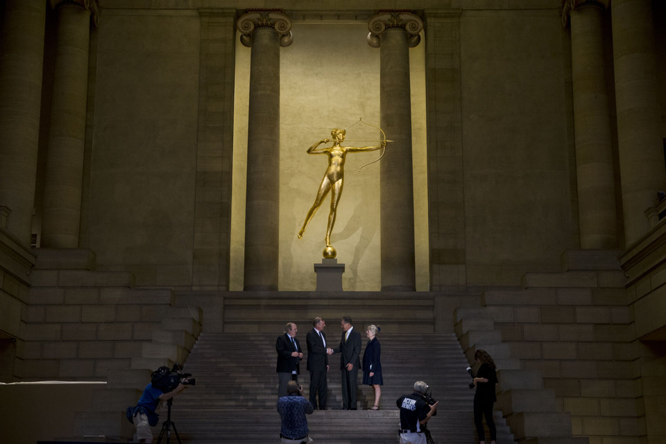 Photo - From left, Andrew Lins, the Neubauer Family Chair of Conservation and Senior Conservator Decorative Arts and Sculpture; Timothy Rub, the George D. Widener Director and CEO; Thomas C. Woodward, Pennsylvania President for Bank of America; and Kathleen A. Foster, Robert L. McNeil Jr. Senior Curator of American Art; pose for photographs beneath the newly restored sculpture of the Roman goddess Diana, which stands atop the Great Stair Hall at the Philadelphia Museum of Art in Philadelphia, Thursday, July 10, 2014. Acquired by the museum in 1932, the work by Augustus Saint-Gaudens originally crowned one of the early venues for New York's Madison Square Garden, where it served as a weather vane starting in 1893. (AP Photo/Matt Rourke)
