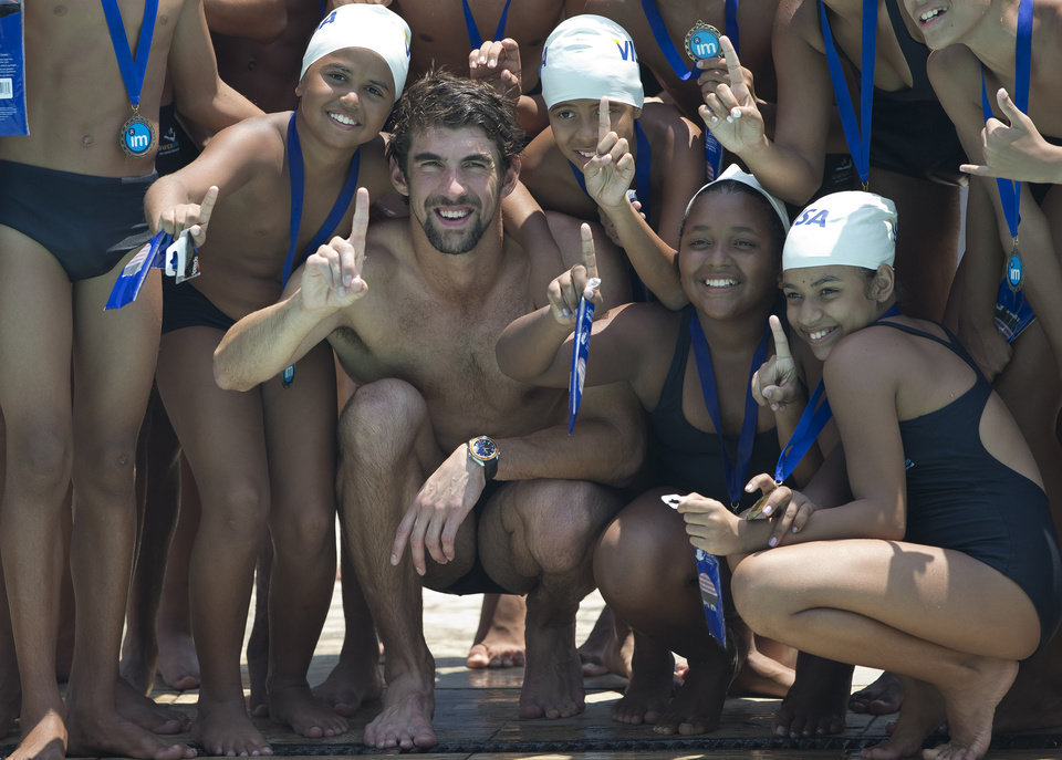 Photo -   U.S. Olympic swimming champion Michael Phelps, center, poses for the media with young swimmers at the Olympic Village Carlos Castilho in the Complexo de Alemao slum in Rio de Janeiro, Brazil, Tuesday, Oct. 30, 2012. Phelps lead a swimming workshop for the children at the Olympic Village which was sponsored by Visa. (AP Photo/Silvia Izquierdo)