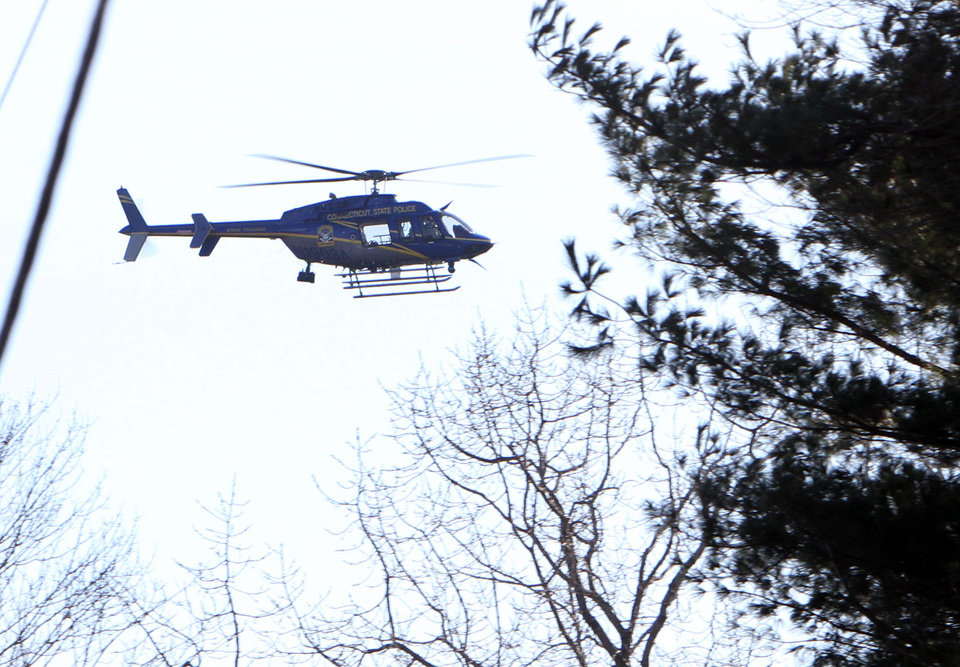 Photo - A Connecticut State Police helicopter hovers over the scene near the Sandy Hook School following a shooting , Friday, Dec. 14, 2012 in Newtown, Conn.(AP Photo/The Journal News, Frank Becerra Jr.) MANDATORY CREDIT, NYC OUT, NO SALES, TV OUT, NEWSDAY OUT; MAGS OUT ORG XMIT: NYWHI129