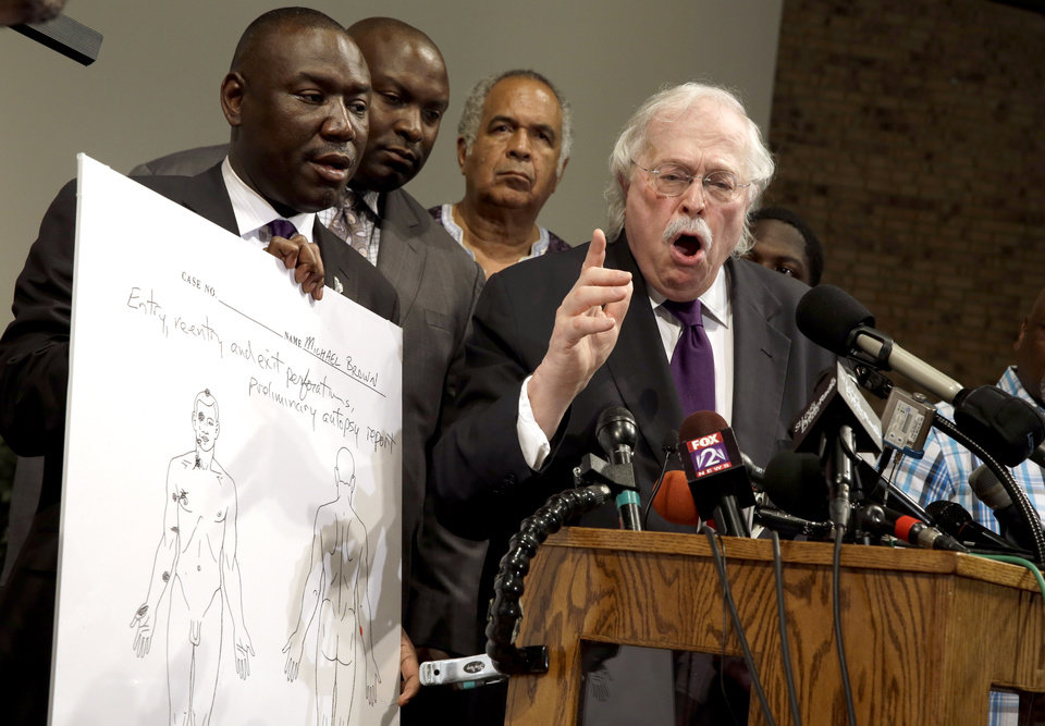 Photo - Dr. Michael Baden, right, speaks as Brown family attorney Benjamin Crump, left, holds a diagram produced during a second autopsy done on 18-year-old Michael Brown Monday, Aug. 18, 2014, in St. Louis County, Mo. The independent autopsy shows Brown was shot at least six times. (AP Photo/Jeff Roberson)
