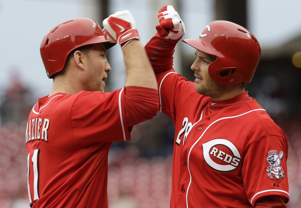 Photo - Cincinnati Reds' Chris Heisey (28) congratulates teammate Todd Frazier after Frazier hit a solo home run off St. Louis Cardinals starting pitcher Lance Lynn in the first inning of a baseball game on Thursday, April 3, 2014, in Cincinnati. (AP Photo/Al Behrman)
