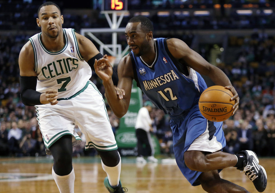 Minnesota Timberwolves' Luc Richard Mbah a Moute (12) drives past Boston Celtics' Jared Sullinger (7) in the second quarter of an NBA basketball game in Boston, Monday, Dec. 16, 2013. (AP Photo/Michael Dwyer)