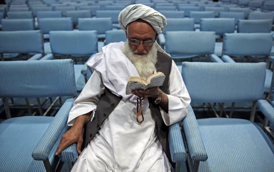 Photo - A supporter of Afghan presidential candidate Abdullah Abdullah, reads the Quran during a gathering of his supporters in Kabul, Afghanistan, Tuesday, July 8, 2014.  Abdullah says he received calls from President Barack Obama and U.S. Secretary of State John Kerry after he refused to accept the preliminary result of the vote citing fraud. He told his supporters the results of the election were fraudulent but asked them to give him a few more days to negotiate. (AP Photo/Massoud Hossaini)