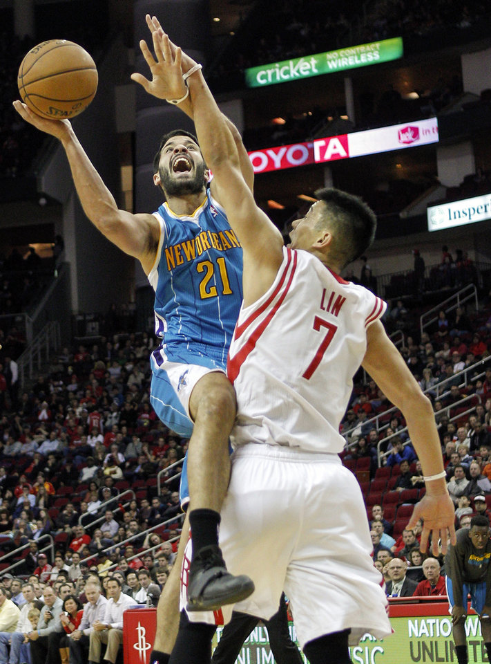 New Orleans Hornets point guard Greivis Vasquez (21) drives past Houston Rockets point guard Jeremy Lin (7) and Houston Rockets power forward Marcus Morris (2) for a layup during the first half of an NBA basketball game on Wednesday, Jan. 2, 2013, in Houston.  (AP Photo/Bob Levey)