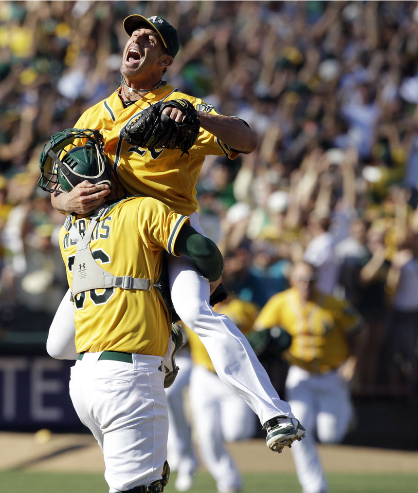 Photo -   Oakland Athletics relief pitcher Grant Balfour, top, and catcher Derek Norris celebrate after their 12-5 win over the Texas Rangers in a baseball game, Wednesday, Oct. 3, 2012 in Oakland, Calif. The A's clinch the AL West title with the win. (AP Photo/Ben Margot)