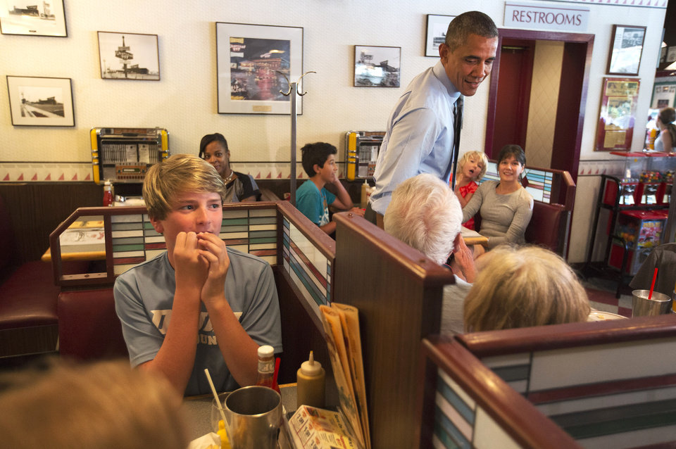 Photo - People react as President Barack Obama stops at the Charcoal Pit in Wilmington, Del., Thursday, July 17, 2014, to meet with Tanei Benjamin, far back at left, who wrote him a letter about her struggles as a single mother. (AP Photo/Jacquelyn Martin)