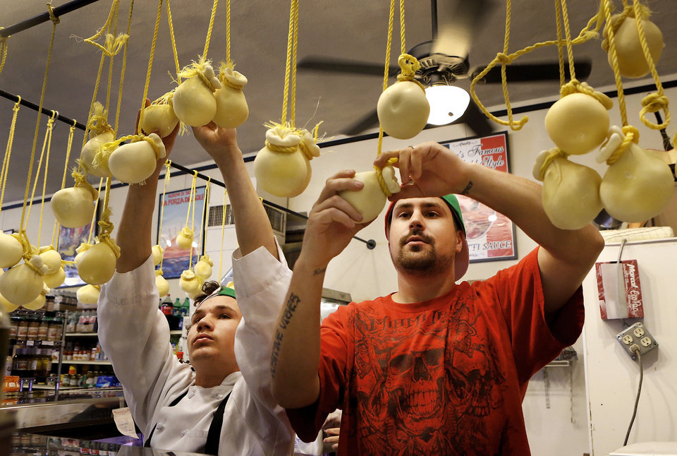 Charlie, left, and Kyle Arpoika hang house-made cheese at Lovera's Italian Market in Krebs, Oklahoma. <strong>Jim Beckel - THE OKLAHOMAN</strong>