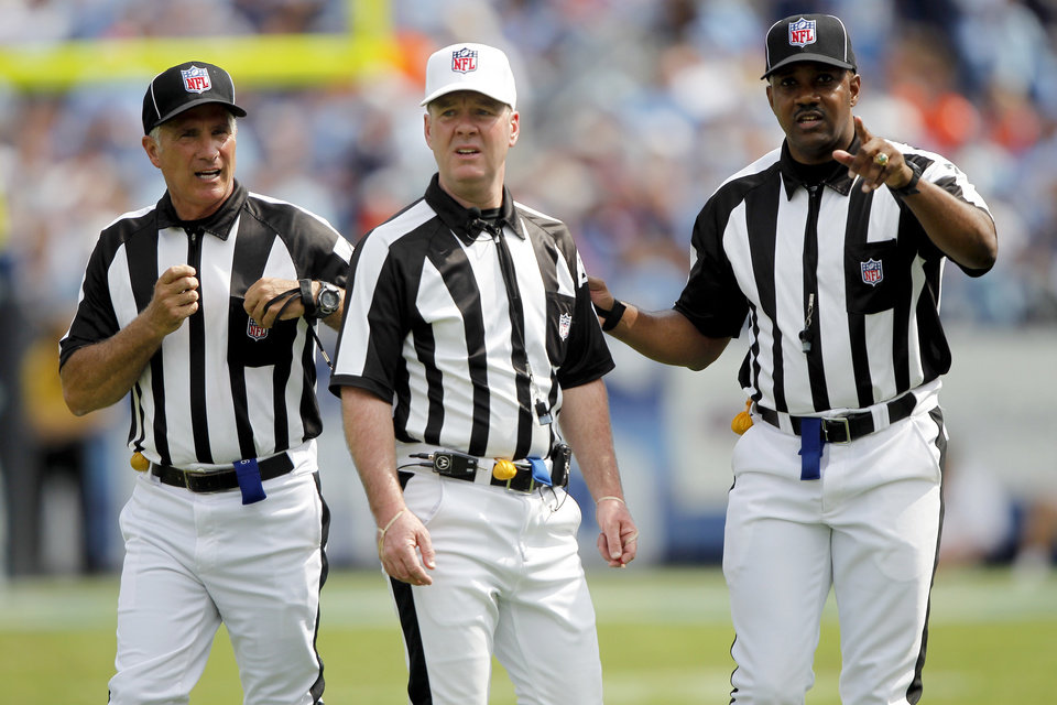 Photo -   FILE - In this Sept. 25, 2011, file photo, officials confer in the third quarter of an NFL football game between the Denver Broncos and the Tennessee Titans in Nashville, Tenn. The NFL and referees' union reached a tentative agreement on Wednesday, Sept. 26, 2012, to end a three-month lockout that triggered a wave of frustration and anger over replacement officials and threatened to disrupt the rest of the season. (AP Photo/Wade Payne, File)