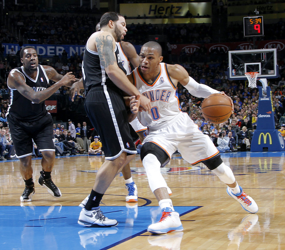 Photo - Oklahoma City's Russell Westbrook (0) drives against Brooklyn Nets' Deron Williams (8) during the NBA basketball game between the Oklahoma City Thunder and the Brooklyn Nets at the Chesapeake Energy Arena on Wednesday, Jan. 2, 2013, in Oklahoma City, Okla. Photo by Chris Landsberger, The Oklahoman
