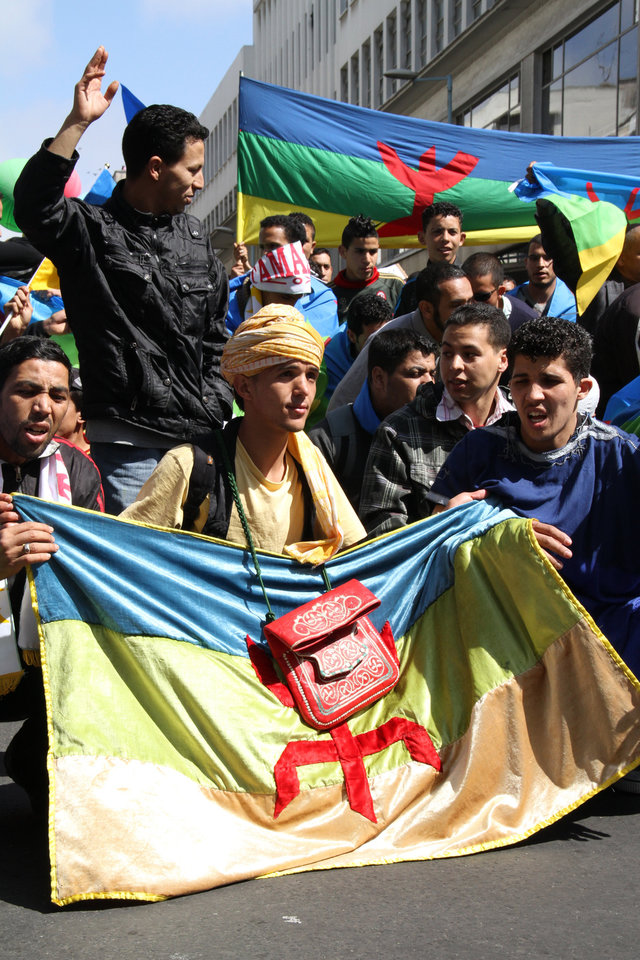 ADVANCE FOR USE SUNDAY, MAY 6, 2012 AND THEREAFTER- In this April 22, 2012, photo, activists kneel with a Berber flag during a march calling for greater rights and autonomy in the Moroccan city of Casablanca. The growing Berber movement, inspired by the Arab Spring, has galvanized North Africa's original inhabitants to push for their political and cultural rights and helped them secure official recognition for their language in Morocco. (AP Photo/Paul Schemm)