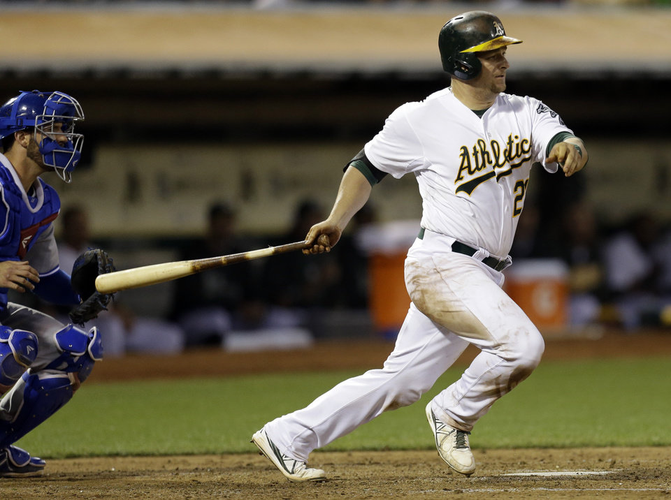 Photo - Oakland Athletics' Stephen Vogt swings for an RBI single off Toronto Blue Jays' Esmil Rogers in the fifth inning of a baseball game Monday, July 29, 2013, in Oakland, Calif. (AP Photo/Ben Margot)