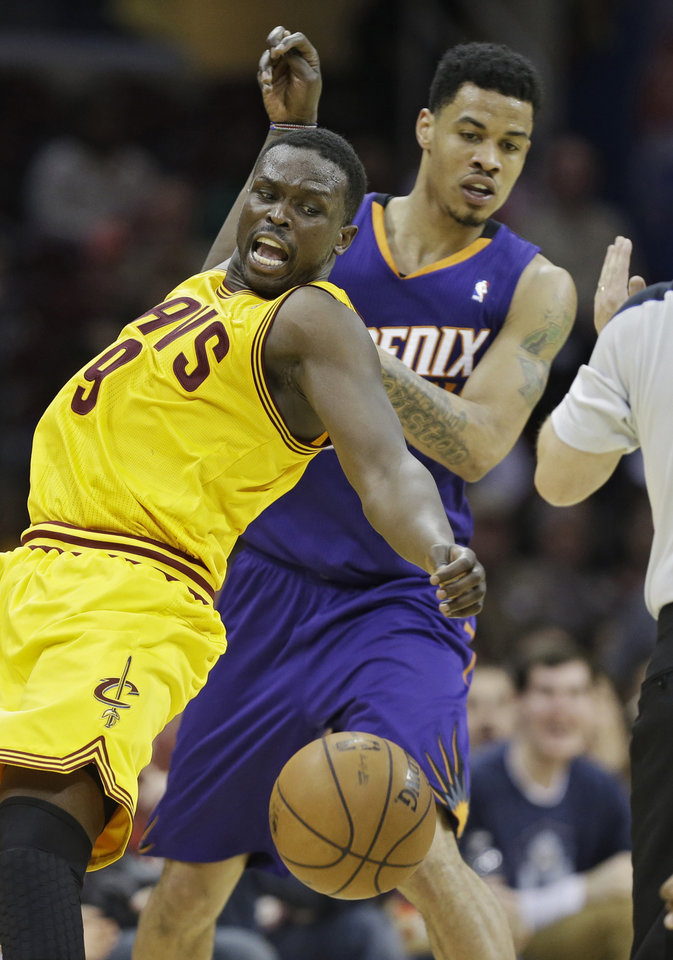 Photo - Cleveland Cavaliers' Luol Deng (9), from Sudan, is fouled by Phoenix Suns' Gerald Green in the fourth quarter of an NBA basketball game, Sunday, Jan. 26, 2014, in Cleveland. Phoenix won 99-90. (AP Photo/Mark Duncan)