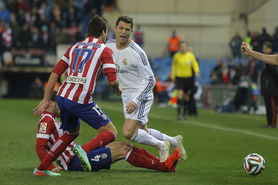 Photo - Real's Cristiano Ronaldo in action with Atletico's Mario Suarez, left, during a semi final, 2nd leg, Copa del Rey soccer match between Atletico de Madrid and Real Madrid at the Vicente Calderon stadium in Madrid, Spain, Tuesday, Feb. 11, 2014. (AP Photo/Andres Kudacki)