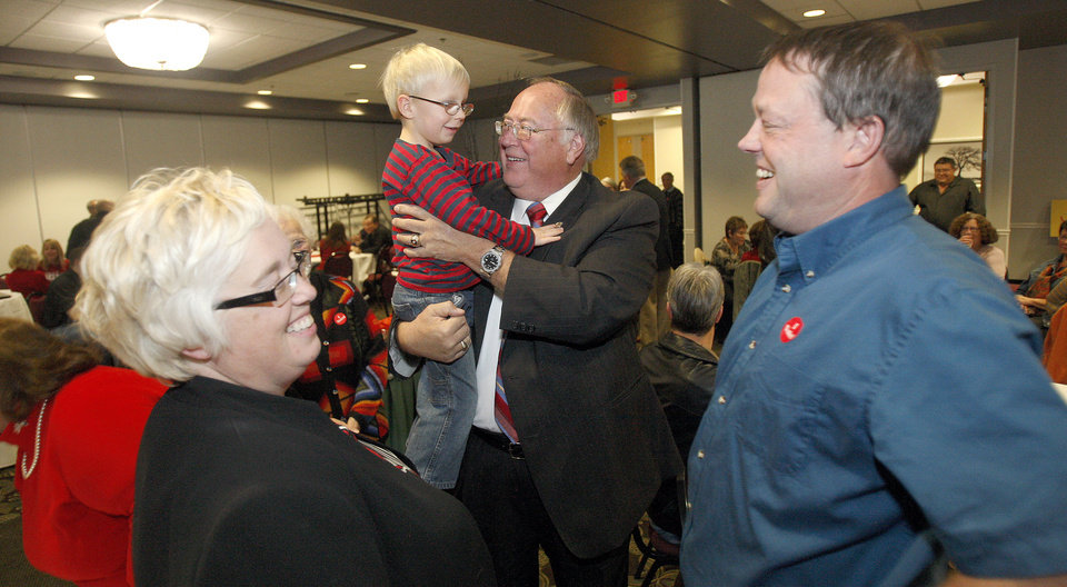 Photo -   Minnesota senator from District 29 Dave Senjem meets Spencer Bradford, 5, while waiting for election returns at the Olmsted County Minnesota GOP event, Tuesday, Nov. 6, 2012 at the Ramada Inn and Convention Center in Rochester, Minn. At left is Bradford's mother, Abby, and right is his father, Chuck Bradford. The Bradfords are from Mantorville, Minn., and Chuck is currently on the city council and running for mayor of Mantorville on today's ballot. (AP Photo/The Rochester Post-Bulletin, Scott Jacobson)