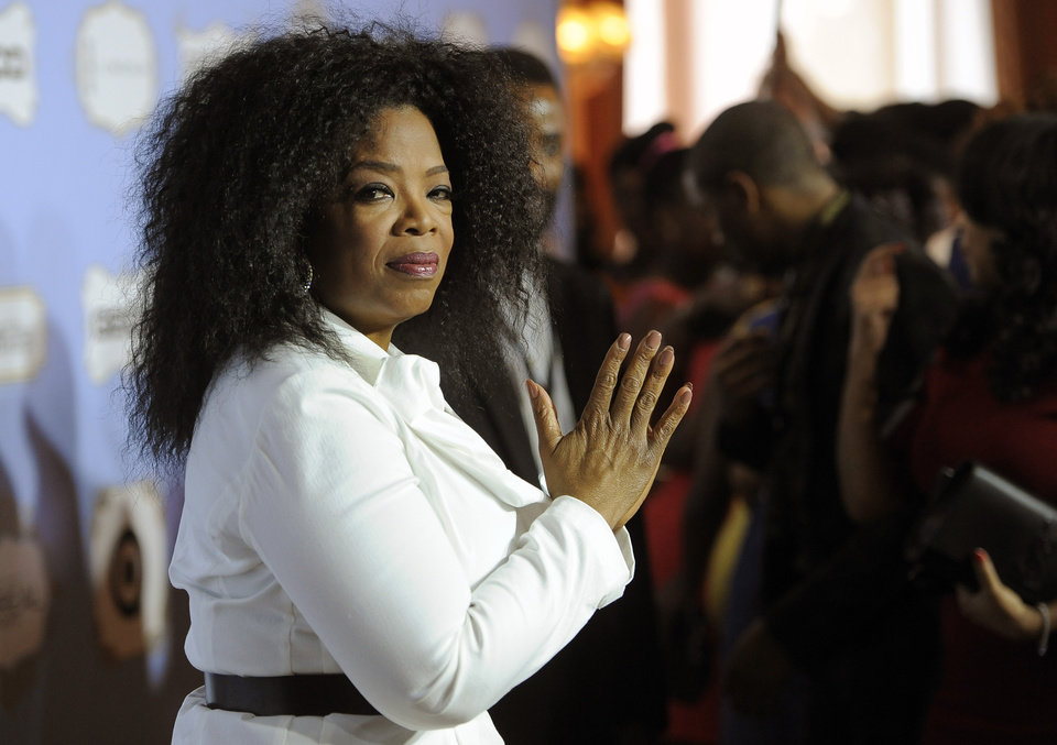 Photo - Oprah Winfrey, recipient of the Power Award, looks down the carpet at the 6th Annual Black Women in Hollywood Luncheon at the Beverly Hills Hotel on Thursday, Feb. 21, 2013 in Los Angeles. (Photo by Chris Pizzello/Invision/AP)