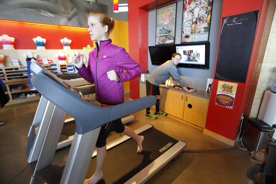 Katie Kramer runs on a treadmill Wednesday as Josh Lacan does a video analysis for fitting running shoes at Red Coyote shoe store in Oklahoma City. Photo By Steve Gooch, The Oklahoman
