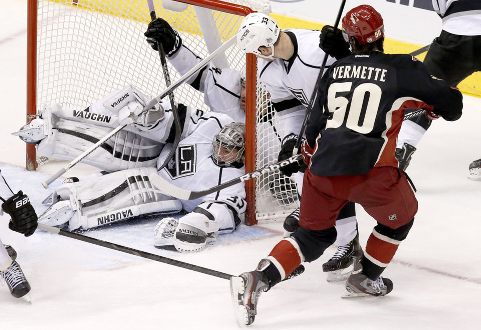 Photo - Phoenix Coyotes' Antoine Vermette (50) scores against Los Angeles Kings' Jonathan Quick (32) as Kings' Willie Mitchell (33) defends and Justin Williams, top left, collides with Quick inside the net during the third period of an NHL hockey game, Tuesday, Jan. 28, 2014, in Glendale, Ariz.  The Coyotes defeated the Kings 3-0. (AP Photo/Ross D. Franklin)