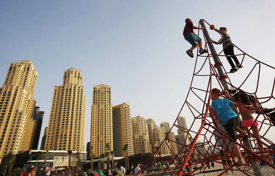 Photo - In this Saturday, April 19, 2014 photo, children play on the beach in Dubai, United Arab Emirates. Most of the luxury towers along the beach have been built only in the past decade. Some are homes to foreign professionals working in the Gulf commercial hub, others vacation properties or a place to park some cash for wealthy businesspeople from Russia, Asia and nearby Saudi Arabia. (AP Photo/Kamran Jebreili)