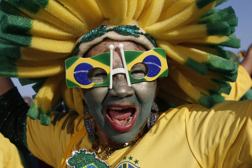 Photo - A Brazilian national soccer team fan cheers as she waits for the live broadcast of the World Cup quarterfinals' match between Brazil and Colombia, inside the FIFA Fan Fest area on Copacabana beach, in Rio de Janeiro, Brazil, Friday, July 4, 2014. (AP Photo/Silvia Izquierdo)