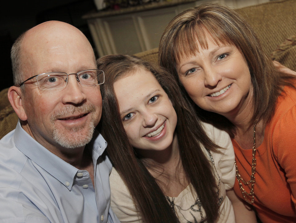 Katie Cooke, middle, poses for a photo with her parents, Mike Cooke and Carrie Cooke, at their home in Bethany, Okla., Thursday, Feb. 23, 2012. Katie Cooke has battled heart problems her whole life. Photo by Nate Billings, The Oklahoman