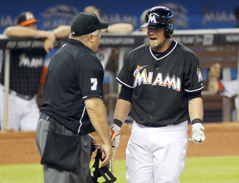 Photo - Miami Marlins' Casey McGehee, right, argues a called third strike with home plate umpire Brian O'Nora to end the fifth inning against the Milwaukee Brewers in a baseball game in Miami, Saturday, May 24, 2014. (AP Photo/Joe Skipper)