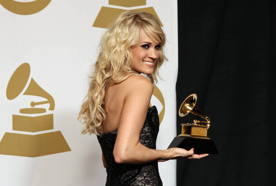 "Carrie Underwood poses backstage with the award for best country solo performance for ""Blown Away"" at the 55th annual Grammy Awards on Sunday, Feb. 10, 2013, in Los Angeles. (Photo by Matt Sayles/Invision/AP) ORG XMIT: CASH198"