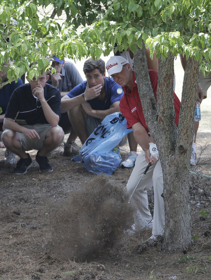 Photo - Steve Stricker hits from behind a tree on the fourth hole during the third round of the U.S. Open golf tournament in Pinehurst, N.C., Saturday, June 14, 2014. (AP Photo/Eric Gay)