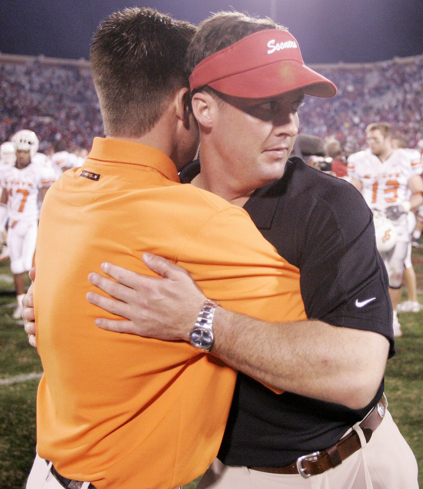 Photo - EMBRACE, HUG: OSU head coach Mike Gundy embraces his brother Cale Gundy, of the OU coaching staff after the University of Oklahoma (OU Sooners) college football game against the Oklahoma State University (OSU Cowboys) at The Gaylord Family - Oklahoma Memorial Stadium Saturday, November 26, 2005 in Norman, Oklahoma. This is the 100th Bedlam football game. Doug Hoke /The Oklahoman
