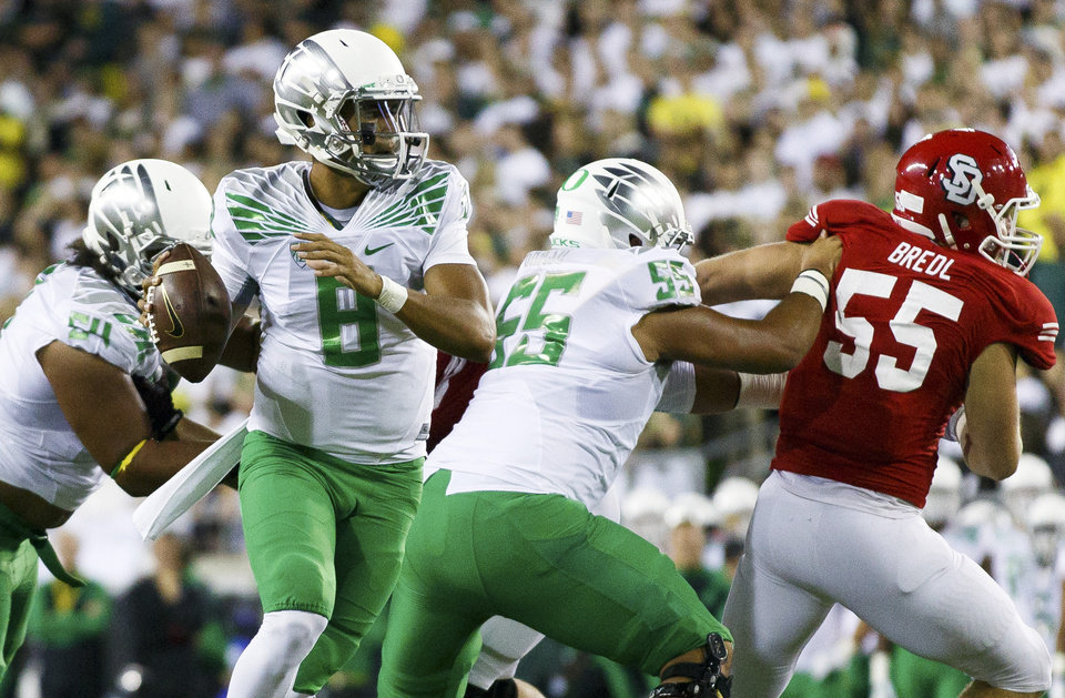 Photo - FILE - In this Aug. 30, 2014, file photo, Oregon quarterback Marcus Mariota (8) looks for an open man during the second quarter of an NCAA college football game in Eugene, Ore. When No. 7 Michigan State plays at No. 3 Oregon on Saturday, the team with the old-school offense will be the unusual one. The Ducks have been at the forefront of the spread revolution. Few teams do it as well as Oregon, though plenty are trying. (AP Photo/Ryan Kang, File)