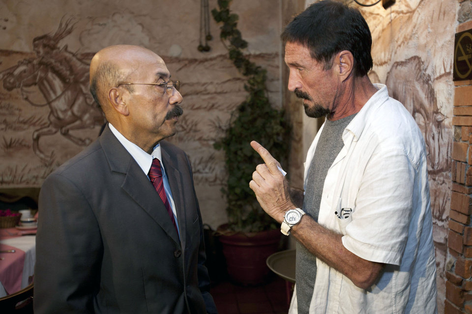 Photo - Software company founder John McAfee talks to his lawyer Telesforo Guerra, right, after giving an interview at a local restaurant in Guatemala City, Tuesday, Dec. 4, 2012.  McAfee, 67, has been identified as a