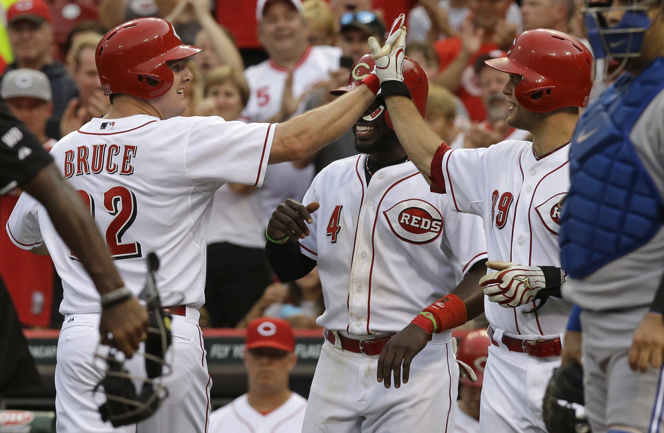 Photo - Cincinnati Reds' Jay Bruce, left, high-fives Devin Mesoraco, right, after Bruce hit a two-run home run off Toronto Blue Jays relief pitcher Todd Redmond in the second inning of a baseball game, Friday, June 20, 2014, in Cincinnati. Brandon Phillips (4) scored on the home run. Mesoraco hit a two-run home run earlier in the inning, nad was coming up to bat again. (AP Photo/Al Behrman)