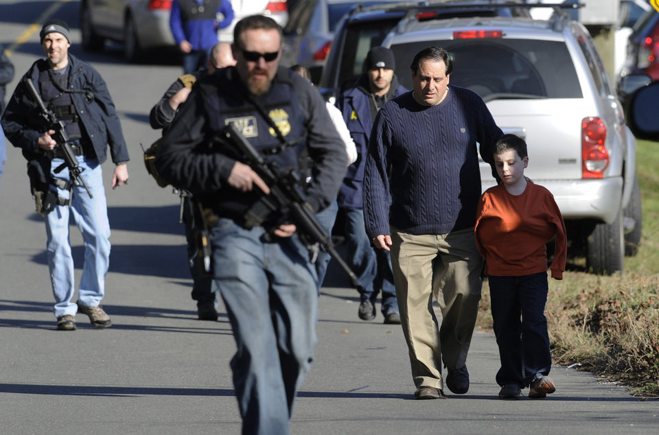 Photo - Parents leave a staging area after being reunited with their children following a shooting at the Sandy Hook Elementary School in Newtown, Conn. where authorities say a gunman opened fire, leaving 27 people dead, including 20 children, Friday, Dec. 14, 2012. (AP Photo/Jessica Hill)