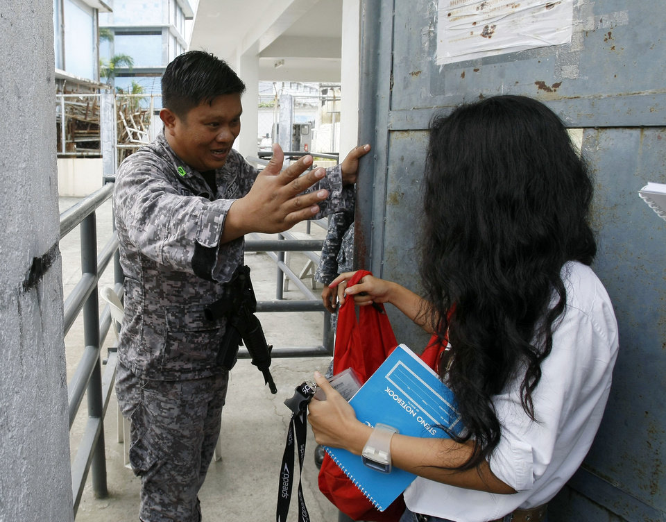 Photo -   A jail guard prevents the media from bringing in cameras and recording equipment as the trial for the Nov. 23, 2009 massacre of at least 57 people, which took place in Maguindanao province in southern Philippines, resumes Wednesday,June 27, 2012, at Camp Bagong Diwa in Taguig southeast of Manila, Philippines. Prosecutor Nena Santos said Wednesday a man who was fatally shot in February was a potential witness in the massacre. The victim was the latest of six witnesses, would-be witnesses and their relatives who have been gunned down since the massacre trial began in 2010. (AP Photo/Bullit Marquez)