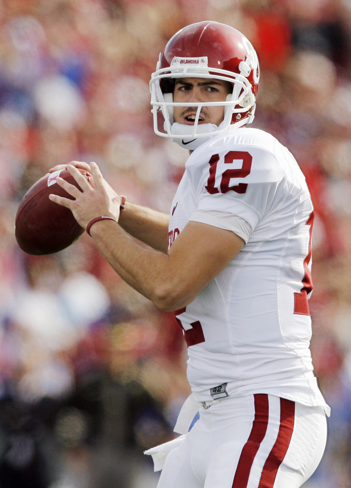 Photo - OU quarterback Landry Jones (12) looks to pass during the first half of the college football game between the University of Oklahoma Sooners (OU) and the University of Kansas Jayhawks (KU) on Saturday, Oct. 24, 2009, in Lawrence, Kan. OU won, 35-13. Photo by Nate Billings, The Oklahoman ORG XMIT: KOD
